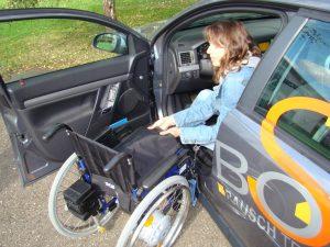 Frau im Auto mit Rollstuhl und dem Faltboy als Hilfsmittel