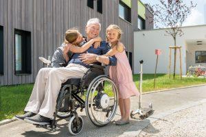 Opa im Rollstuhl mit Enkelkindern